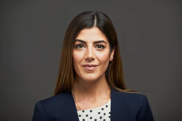 Kopfschuss einer selbstbewussten Geschäftsfrau auf grauem Hintergrund. – Foto