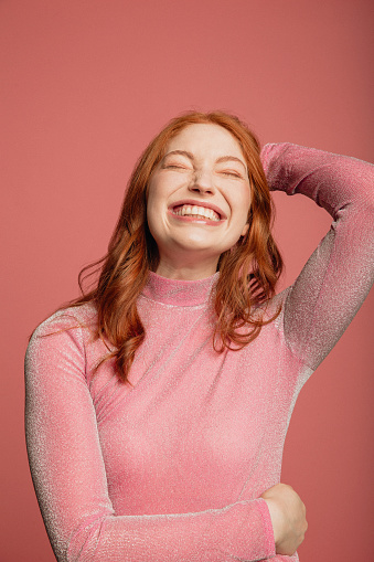 Close-up portrait of a young redhead woman dressed in a pink sparkly top standing in front of a pink background.