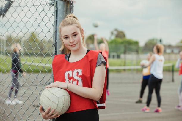 headshot van een tiener meisje dat een netball vasthoudt - netball stockfoto's en -beelden