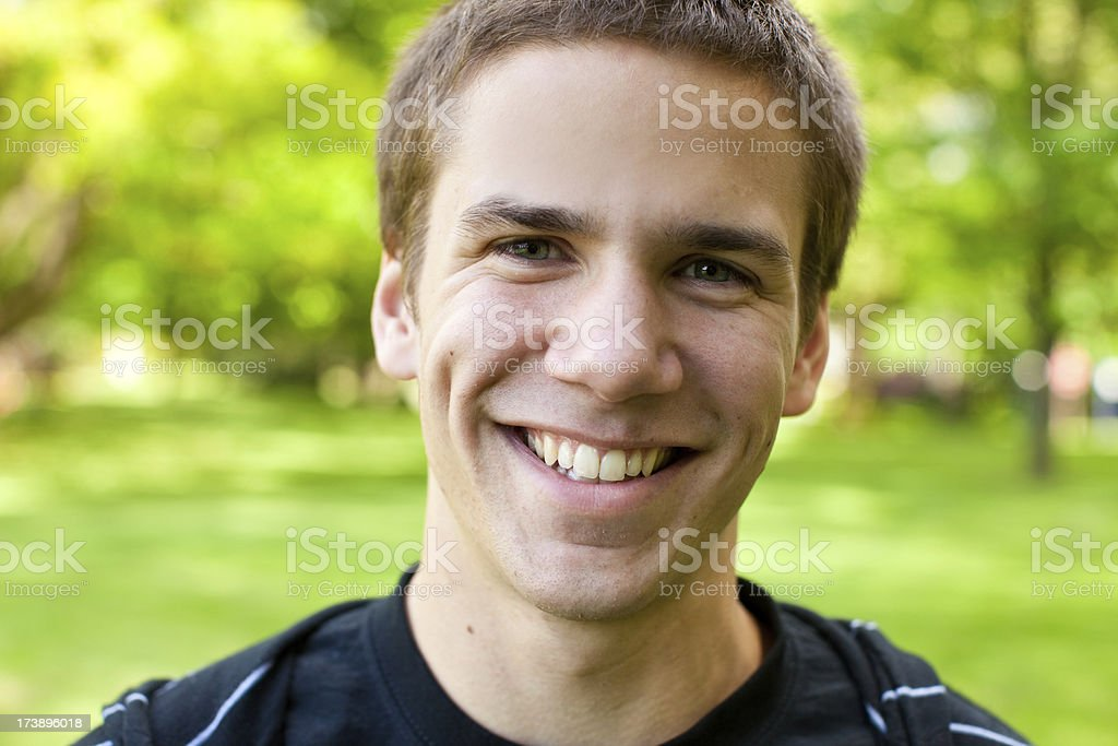 headshot of a young man smiling at camera in park royalty-free stock photo