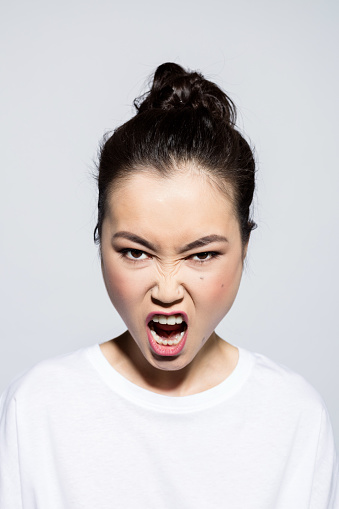 Portrait of frustrated asian young woman wearing white t-shirt, screaming at camera. Studio shot, grey background.