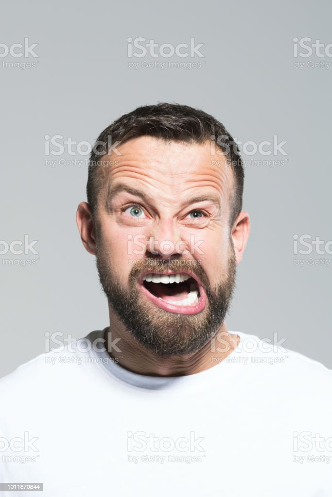 Headshot of angry bearded young man, grey background Portrait of angry bearded young man screaming at camera. Headshot, grey background. 30-34 Years Stock Photo