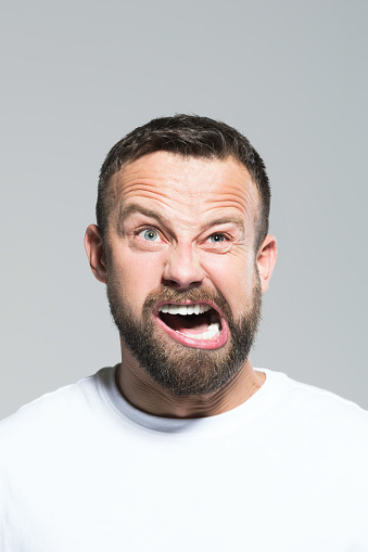 Headshot Of Angry Bearded Young Man Grey Background Stock Photo - Download Image Now