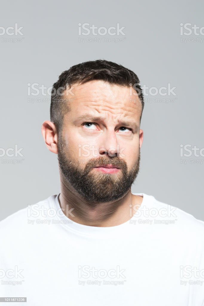 Headshot of bearded young man looking up and wondering, grey background Portrait of pensive bearded young man, looking away. Headshot, grey background. 30-34 Years Stock Photo