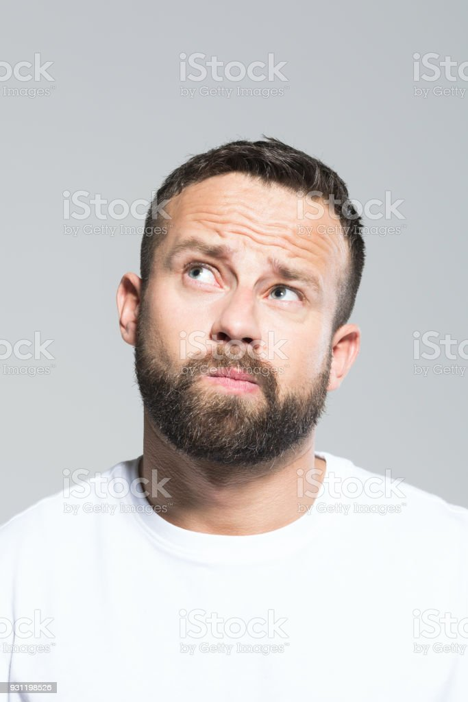 Headshot of bearded young man looking up and wondering, grey background Portrait of worried bearded young man, looking at camera. Headshot, grey background. 30-34 Years Stock Photo
