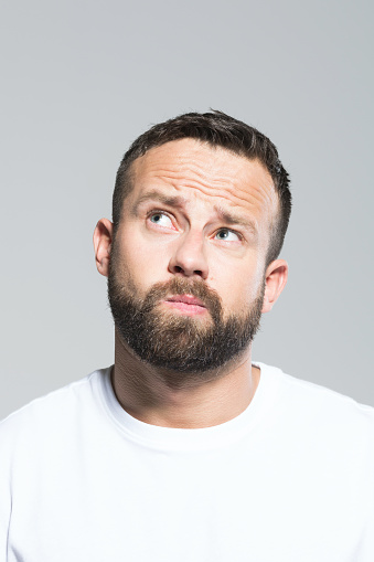 Headshot Of Bearded Young Man Looking Up And Wondering Grey Background Stock Photo - Download Image Now