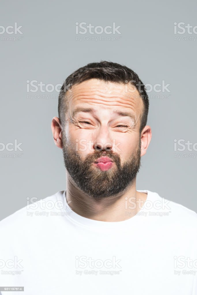 Headshot of bearded young man making funny face, grey background Portrait of bearded young man making funny face. Headshot, grey background. 30-34 Years Stock Photo