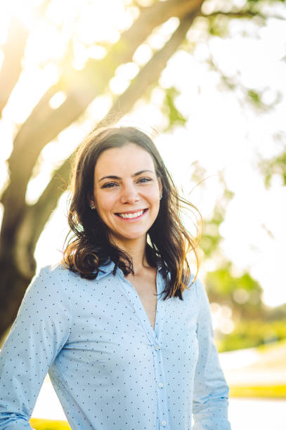 Headshot of beautiful brunette woman in her 30's smiling at the camera stock photo