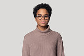 Headshot portrait of beautiful african American millennial woman in glasses and sweater stand isolated on grey studio background, black biracial female wearing spectacles look at camera posing