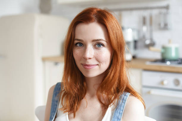 Headshot of charming beautiful young European woman with red shiny hair and freckles cooking or having meal in kitchen interior, looking at camera with cute smile. People and lifestyle concept Headshot of charming beautiful young European woman with red shiny hair and freckles cooking or having meal in kitchen interior, looking at camera with cute smile. People and lifestyle concept redhead stock pictures, royalty-free photos & images