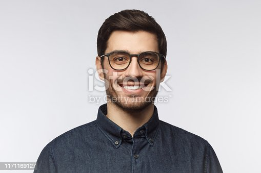 Headshot of cheerful handsome man with trendy haircut and eyeglasses isolated on gray background