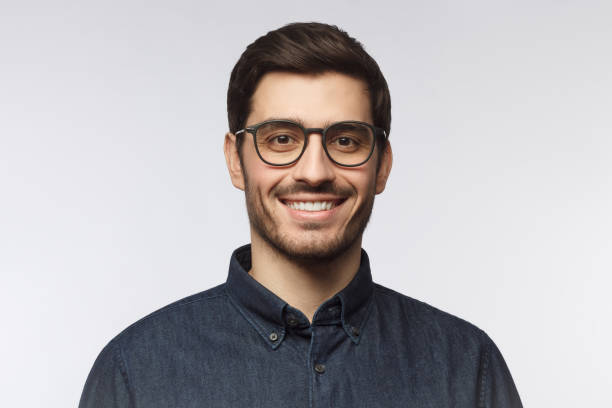 Headshot of cheerful handsome man with trendy haircut and eyeglasses isolated on gray background Headshot of cheerful handsome man with trendy haircut and eyeglasses isolated on gray background male likeness stock pictures, royalty-free photos & images