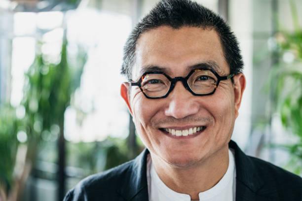 Headshot of Chinese man wearing glasses and smiling stock photo