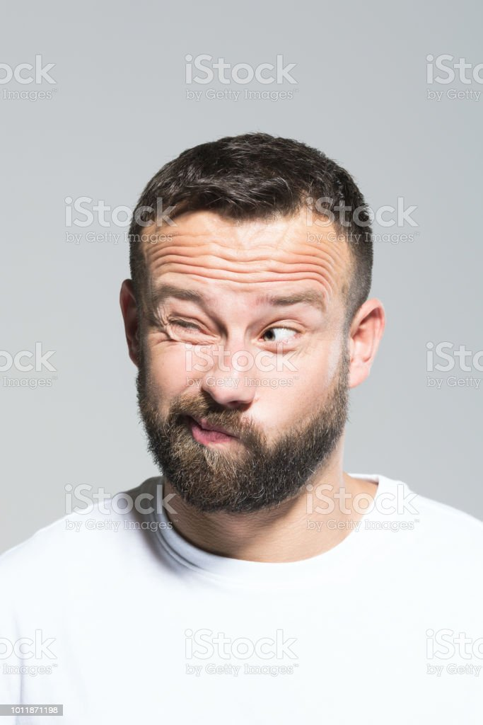Headshot of confused bearded young man, grey background Portrait of disappointed bearded young man, looking away and making a decision. Headshot, grey background. 30-34 Years Stock Photo