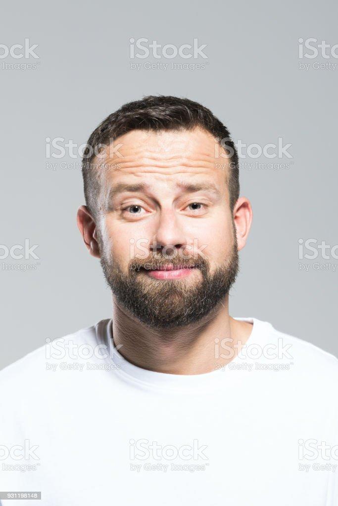 Headshot of cute bearded young man, grey background Portrait of cute bearded young man looking at camera. Headshot, grey background. 30-34 Years Stock Photo
