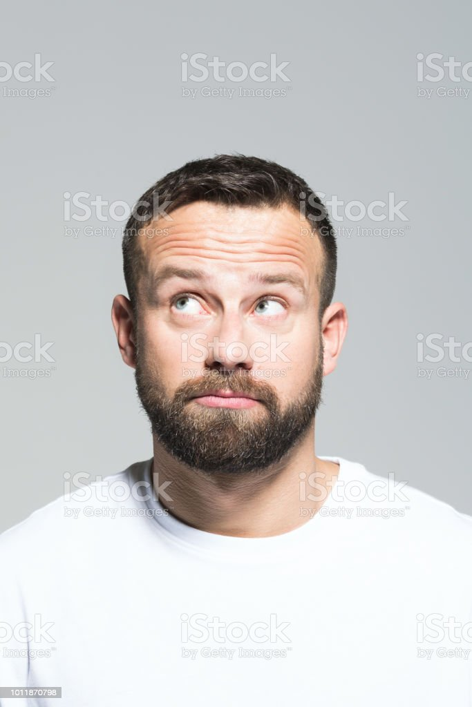Headshot of disappointed bearded young man, grey background Portrait of confused bearded young man, looking away. Headshot, grey background. 30-34 Years Stock Photo