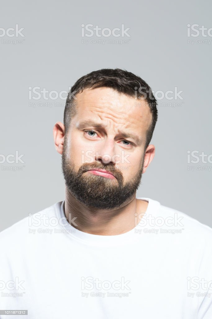 Headshot of disappointed bearded young man, grey background Portrait of unhappy bearded young man, looking at camera. Headshot, grey background. 30-34 Years Stock Photo