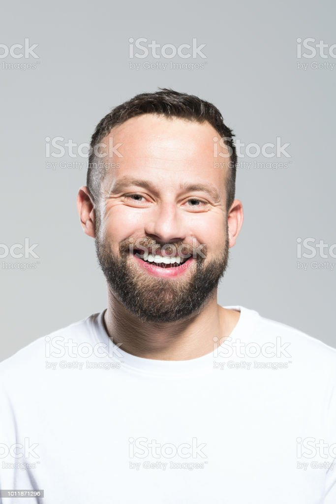 Headshot of excited bearded young man, grey background Portrait of happy bearded young man laughing at the camera. Headshot, grey background. 30-34 Years Stock Photo