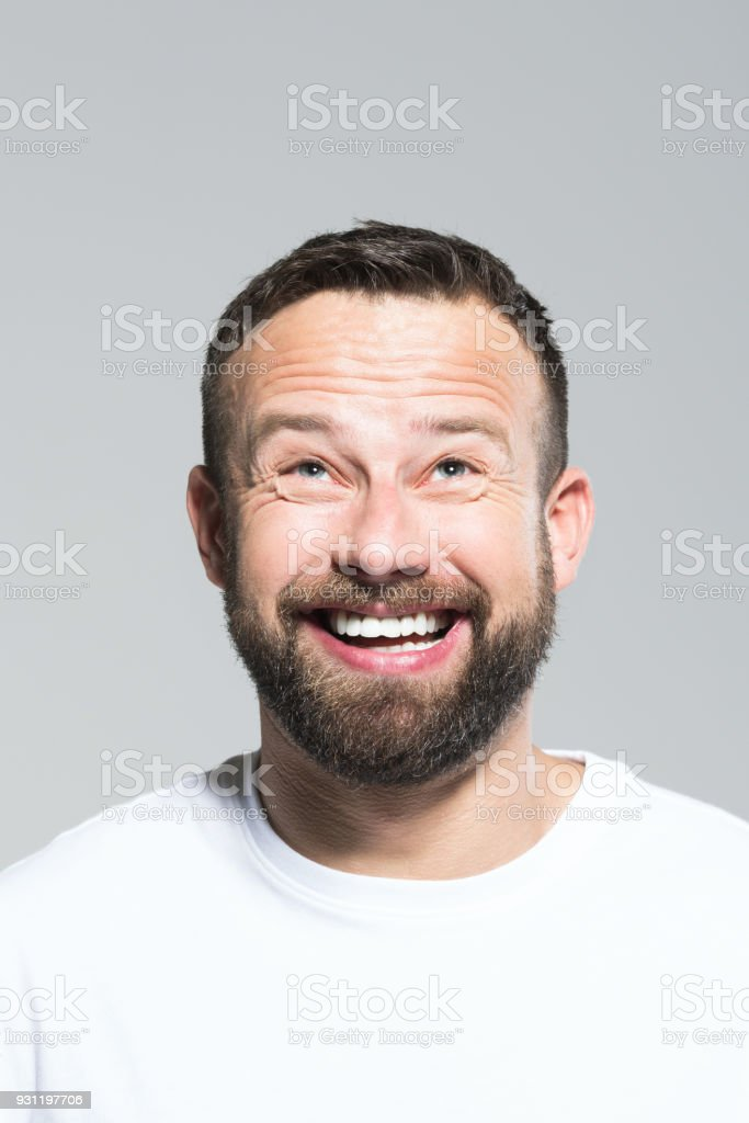 Headshot of excited bearded young man, grey background Portrait of excited bearded young man laughing. Headshot, grey background. 30-34 Years Stock Photo