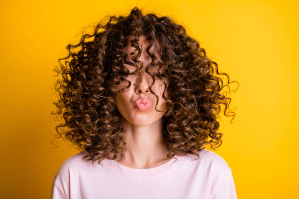 Headshot of girl with curly hairstyle wearing t-shirt send air kiss pouted lips isolated on vivid yellow color background stock photo