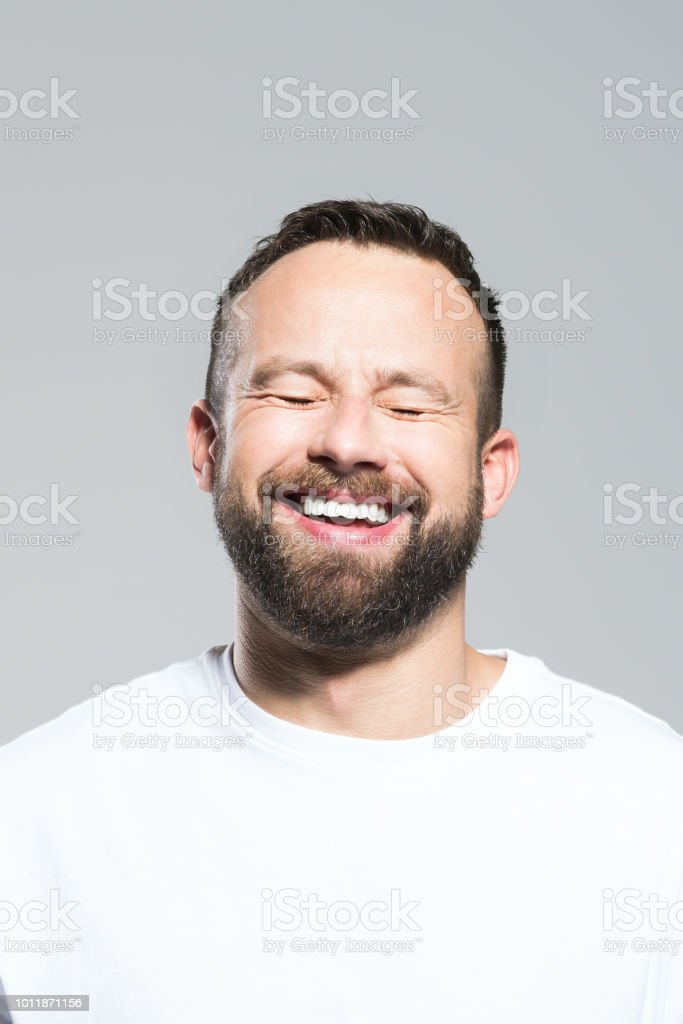 Headshot of happy bearded young man, grey background Portrait of excited bearded young man laughing with eyes closed. Headshot, grey background. 30-34 Years Stock Photo