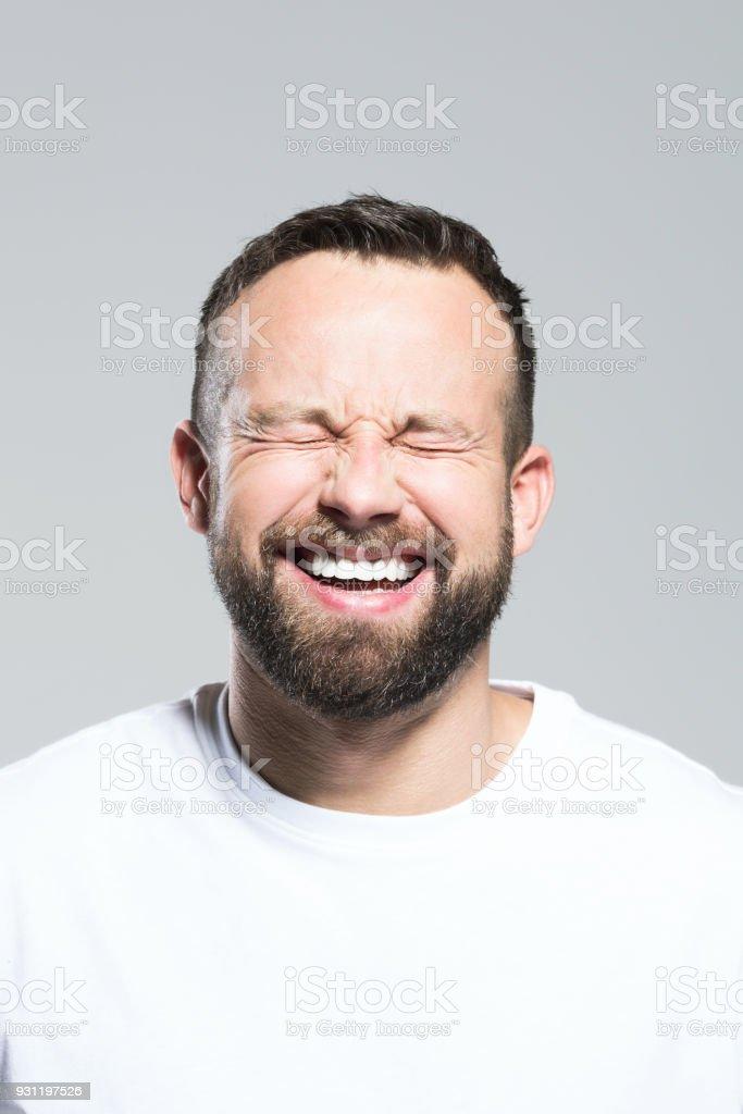 Headshot of happy bearded young man, grey background stock photo