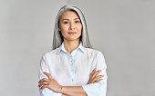 istock Headshot of mature 50 years old Asian business woman on grey background. 1317784594