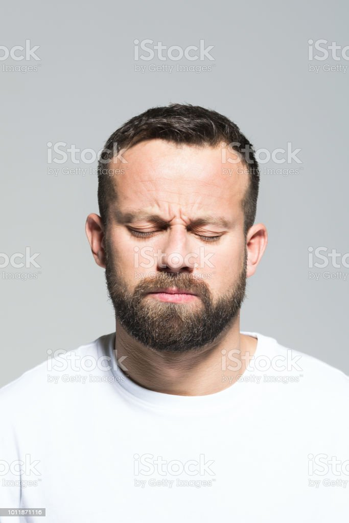 Headshot of pensive bearded young man, grey background Portrait of pensive bearded young man thinking with eyes closed. Headshot, grey background. 30-34 Years Stock Photo