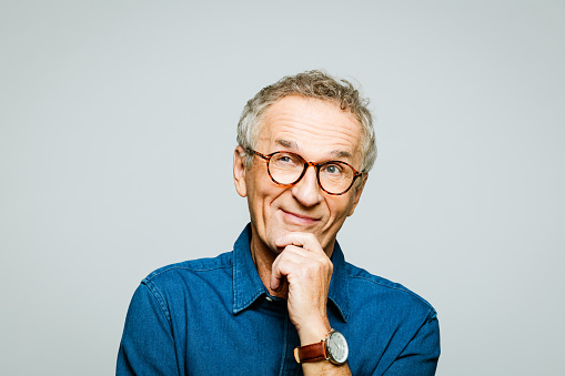 Portrait of elderly man wearing white denim shirt and glasses looking away and smiling with hand on chin. Pleased senior entrepreneur, studio shot against grey background.