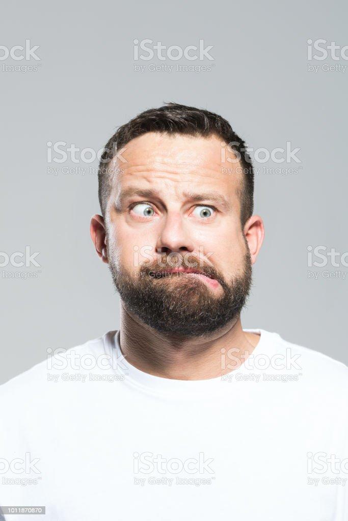 Headshot of shocked bearded young man, grey background Portrait of afraid bearded young man looking away and grimacing. Headshot, grey background. 30-34 Years Stock Photo