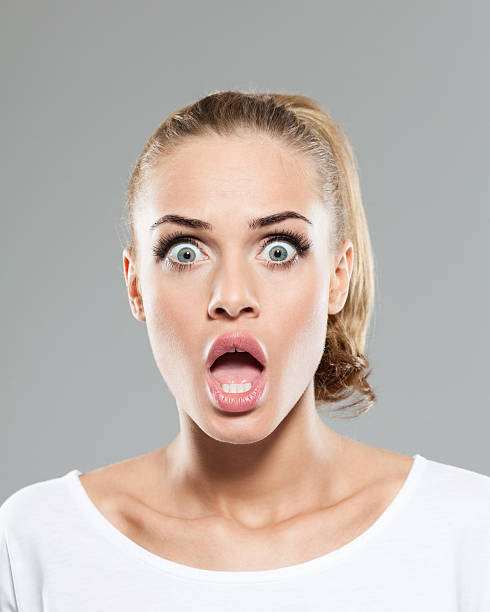 Headshot of shocked blond hair young woman Portrait of shocked blonde young woman wearing white t-shirt and jeans, staring at camera with mouth open, rolling eyes. Studio shot, grey background. gasping stock pictures, royalty-free photos & images