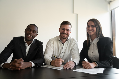 995734014 istock photo Headshot of smiling diverse employees look at camera in office 1265525649