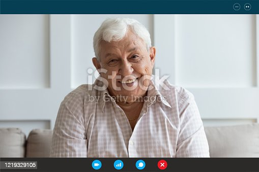 Headshot portrait screen view of smiling senior grandfather talk on video call on laptop with relatives or kids, happy elderly man speak have pleasant online Webcam conversation on computer at home