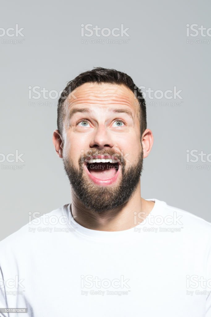 Headshot of surprised bearded young man, grey background Portrait of excited bearded young man looking up and laughing. Headshot, grey background. 30-34 Years Stock Photo