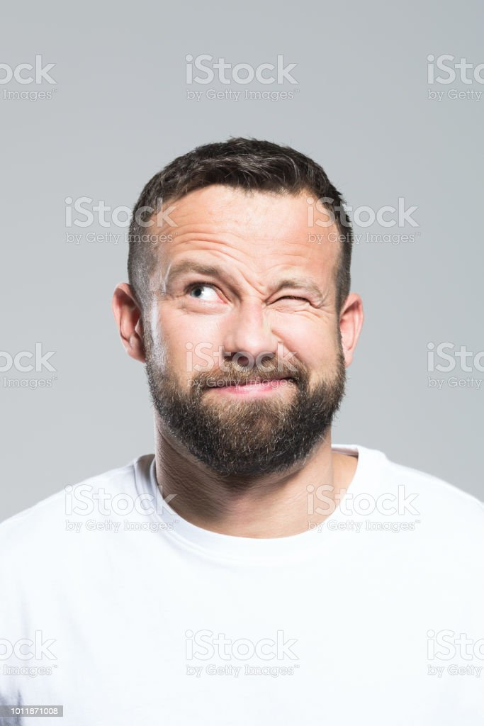 Headshot of surprised bearded young man, grey background Portrait of bearded young man blinking, making a decision. Headshot, grey background. 30-34 Years Stock Photo