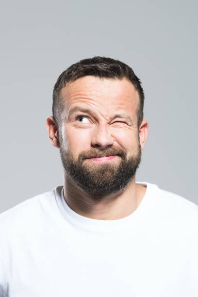 Headshot of surprised bearded young man, grey background Portrait of bearded young man blinking, making a decision. Headshot, grey background. blinking stock pictures, royalty-free photos & images