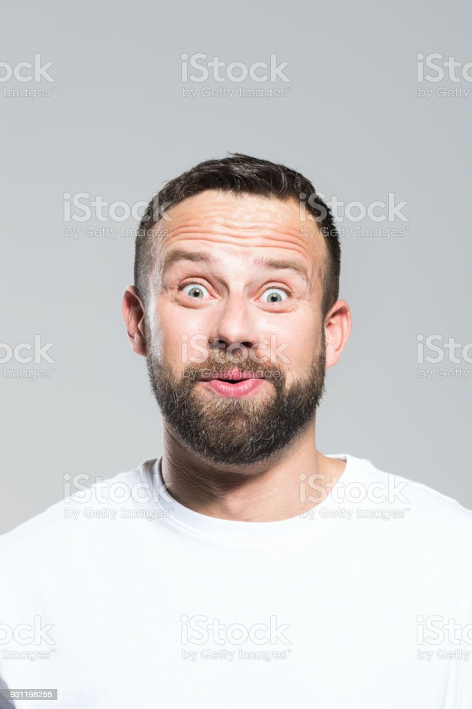 Headshot of surprised bearded young man, grey background Portrait of surprised bearded young man staring at camera and whistling. Headshot, grey background. 30-34 Years Stock Photo