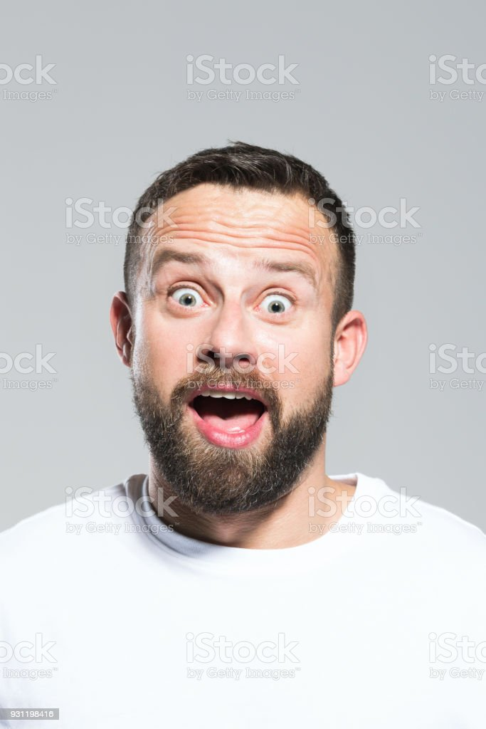 Headshot of surprised bearded young man, grey background Portrait of surprised bearded young man staring at camera with mouth open. Headshot, grey background. 30-34 Years Stock Photo