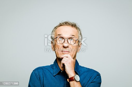 Portrait of elderly man wearing white denim shirt and glasses looking up with hand on chin. Thoughtful senior entrepreneur, studio shot against grey background.