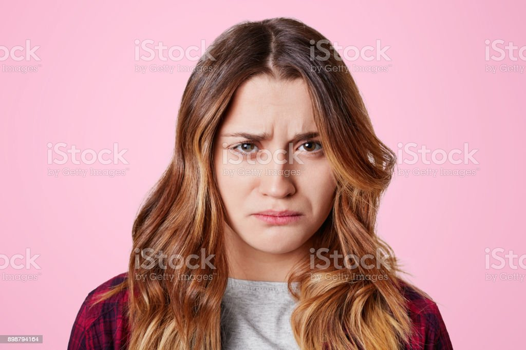 Headshot of unhappy sorrorful female curves lips, looks desperately at camera, being upset to hear bad news or about failing exams, isolated over pink background. Miserable gloomy pretty woman stock photo