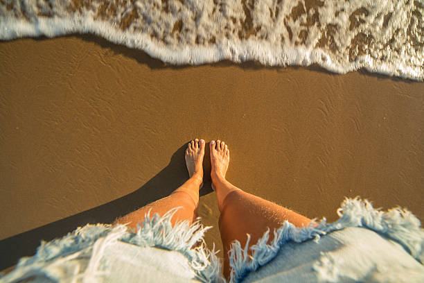 headshot of woman's feet on sandy beach - woman leg beach pov stock photos and pictures
