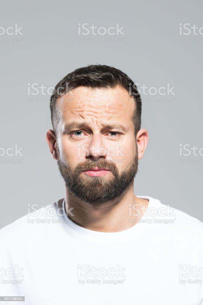 Headshot of worried bearded young man, grey background Portrait of worried bearded young man, looking at camera. Headshot, grey background. 30-34 Years Stock Photo