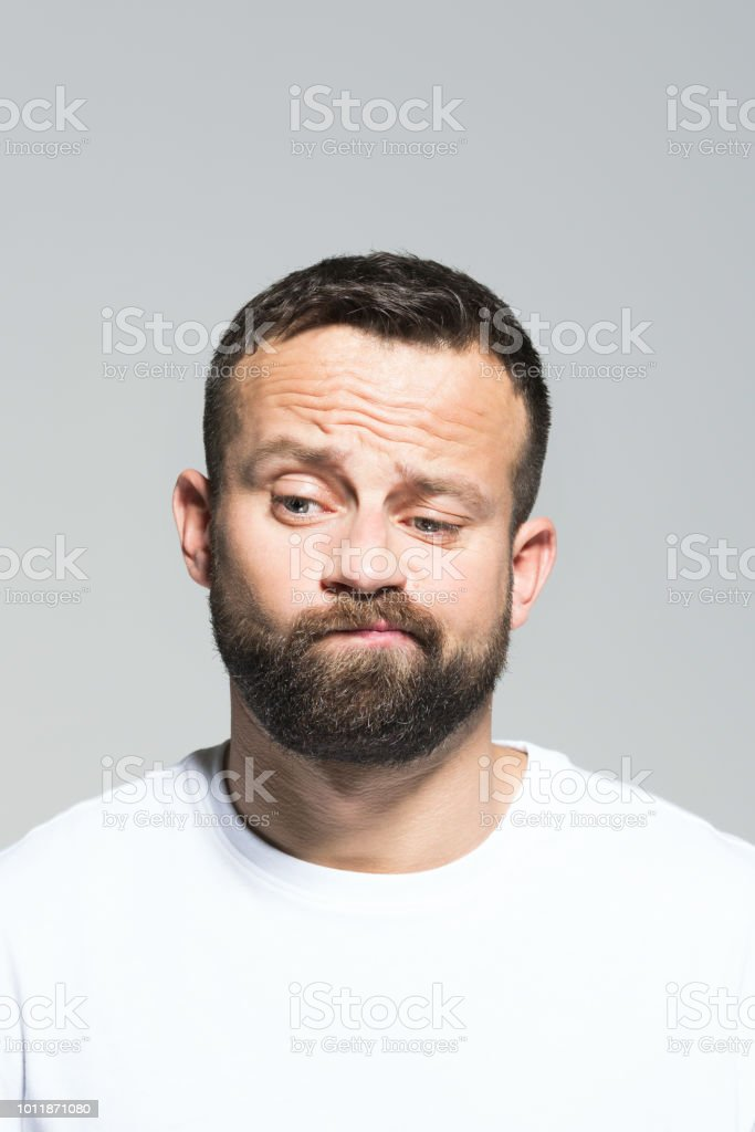 Headshot of worried bearded young man making a decision Portrait of disappointed bearded young man, looking away and making a decision. Headshot, grey background. 30-34 Years Stock Photo