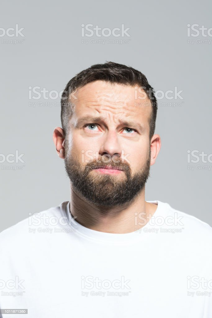 Headshot of worried bearded young man making a decision Portrait of pensive bearded young man, looking up and making a decision. Headshot, grey background. 30-34 Years Stock Photo