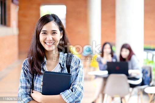 istock Headshot of young happy attractive asian student smiling and looking at camera with friends on outdoor university background. Asian woman in self future education or personalized learning concept. 1150975772