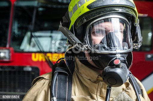 Headshot on fireman wearing full protection equipment in front of truck