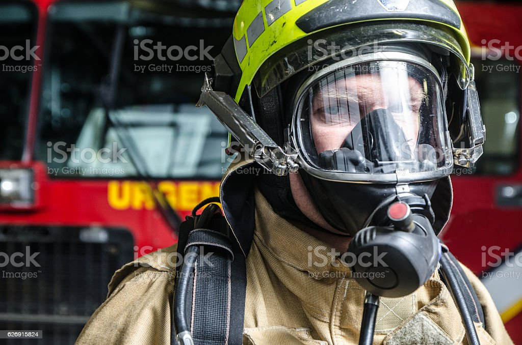 Headshot on fireman wearing full protection equipment and truck stock photo