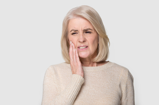 istock Headshot portrait mature woman touches cheek suffers from tooth ache 1151796065