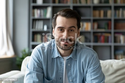 Head shot millennial guy sit on sofa in living room makes video call looks at camera, conversation by distant videocall, distance hiring job interview process, tutor and trainee study on-line concept