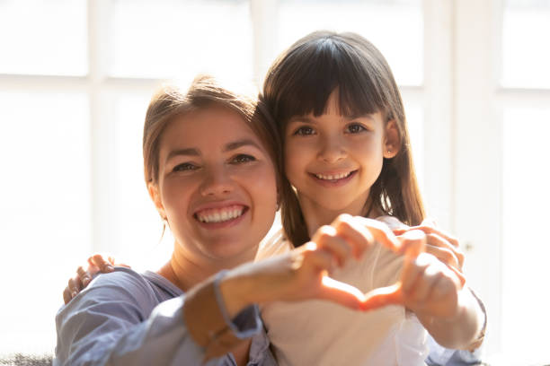 headshot portrait mother and daughter make heart shape with hands - organ donation stock pictures, royalty-free photos & images